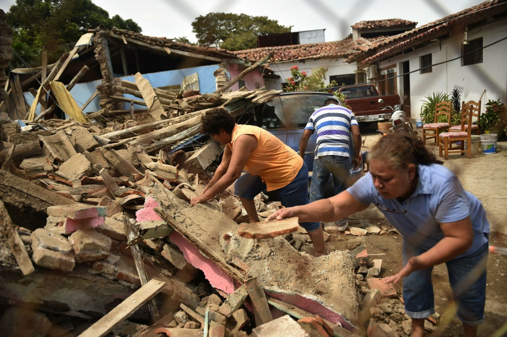 People search on September 8, 2017 amid the rubble of buildings which collapsed in Juchitan de Zaragoza, state of Oaxaca, after an 8.2 earthquake that hit Mexico's Pacific coast overnight. Mexico's most powerful earthquake in a century killed at least 35 people, officials said, after it struck the Pacific coast, wrecking homes and sending families fleeing into the streets.