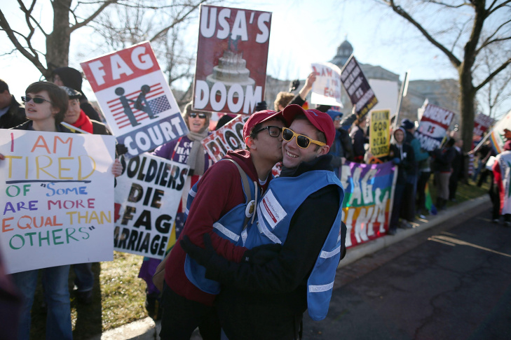 WASHINGTON, DC - MARCH 26: David Elizondo (R) gets a kiss from a friend in front of protesters against gay marriage during a rally in front of the U.S. Supreme Court, on March 26, 2013 in Washington, DC. Today the high court is scheduled to hear arguments in California's Proposition 8, the controversial ballot initiative that defines marriage as between a man and a woman.