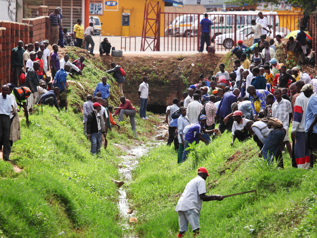 The people of Rwanda are required to take part in the national clean-up day, Umuganda, on the last Saturday of every month. Above: getting grass under control in Kigali, the capital city.