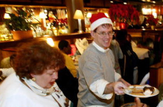 Volunteers Jeff Steger, with Santa hat passes out cookies and Diane Dabkowski (L) puts food into a container as homeless and underprivileged inner city children and their families sit down for a Christmas dinner at the District Chophouse & Brewery restaurant 25 December 2003 in Washington, DC.