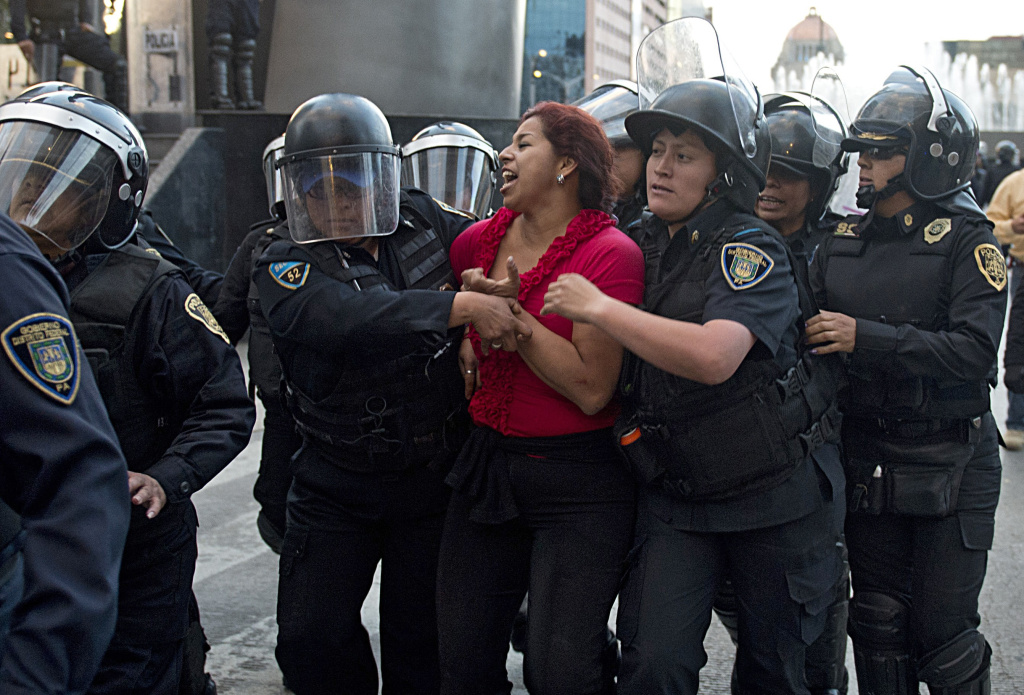 Riot policemen arrest a teacher during a protest against the education reform in Mexico City on November 26, 2013. President Enrique Pena Nieto pushed through Congress changes to the constitution in order to require teachers to undergo mandatory performance appraisals.  AFP PHOTO /  Yuri CORTEZ        (Photo credit should read YURI CORTEZ/AFP/Getty Images)