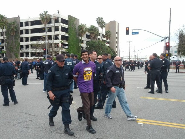 A man flashes the camera a smile as he's led away in handcuffs. Arrests have begun at a May Day rally centered on LAX International Airport.