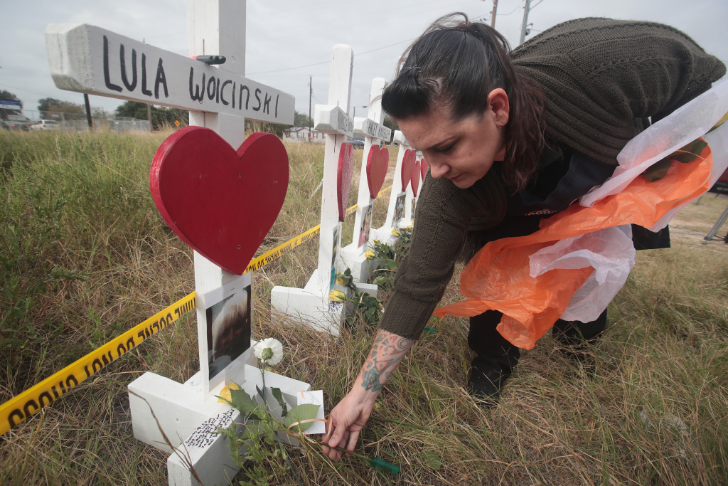 Joyce Mires leaves flowers at a memorial where 26 crosses were placed to honor the 26 people killed at the First Baptist Church of Sutherland Springs on November 5, 2017 in Sutherland Springs, Texas.
