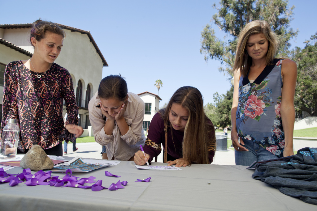 Sofia Schugar, left, Natalie Sharp, Lenox Peterson and Isabel Annino stop at the domestic violence awareness table at Occidental College to write phrases in support of sexual assault awareness on campus.