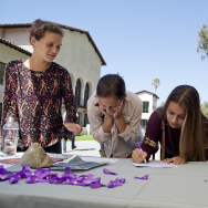 "Sofia Schugar, left, Natalie Sharp, Lenox Peterson and Isabel Annino stop at the domestic violence awareness table at Occidental College to write in support of sexual assault awareness on campus. They are cross-country running recruits who will attend Occidental next year. ""A girl going to college shouldn't have to worry about dating violence,"" Sharp said. ""She should only have to worry about her education."""