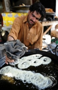 A Pakistani vendor drizzles butter into a pan of hot oil to fry sweets locally known as 'jalebi' at a market in Islamabad.