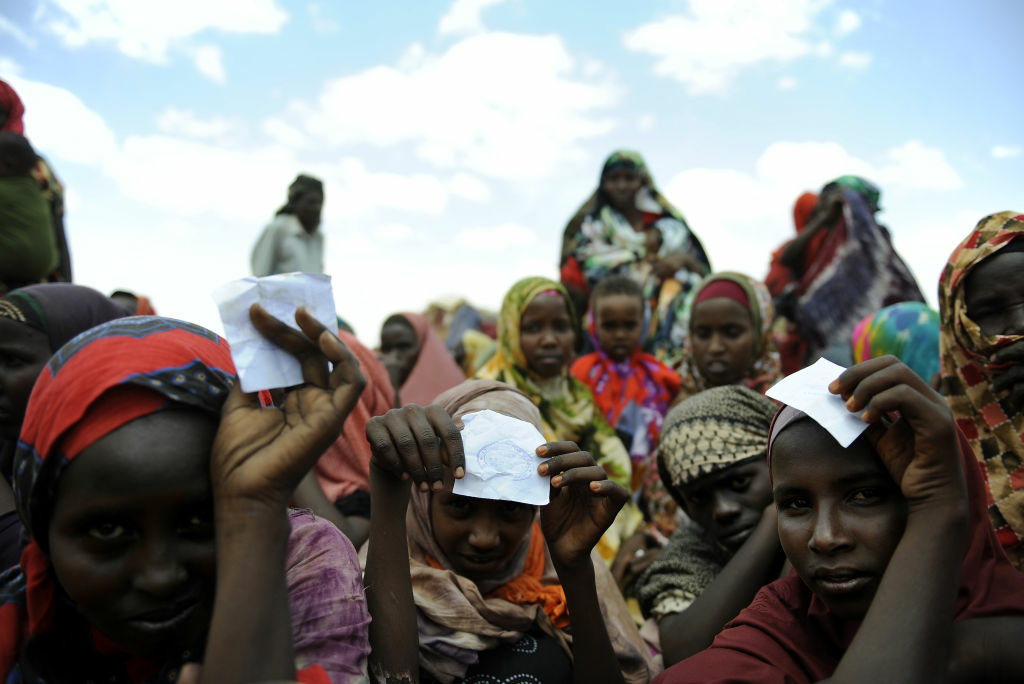 Young displaced Somali women along with other newly arrived refugees wait to be registered at a centre in Doolow on October 30, 2011, south western Somalia.