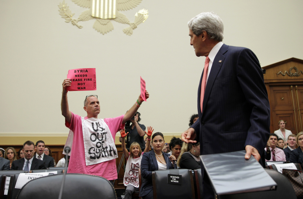 Members of CodePink, Tighe Barry (L) and Medea Benjamin (2nd L) protest as U.S. Secretary of State John Kerry (R) arrives at a hearing on