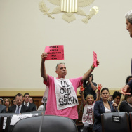 "Members of CodePink, Tighe Barry (L) and Medea Benjamin (2nd L) protest as U.S. Secretary of State John Kerry (R) arrives at a hearing on ""Syria: Weighing the Obama Administration's Response"" before the House Foreign Affairs Committee September 4, 2013 on"