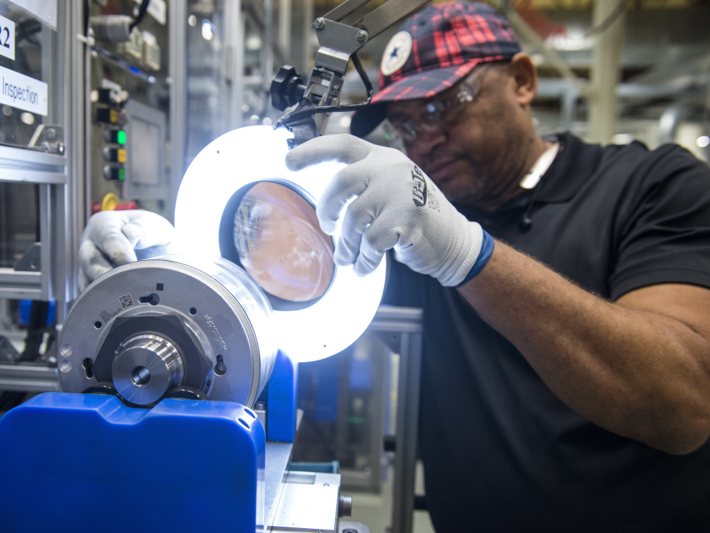 An employee inspects a component for hybrid electric vehicle motors at the Toshiba International Corp. manufacturing facility in Houston.