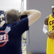 In this Sept. 26, 2014 photo, Cleveland Cavaliers' LeBron James poses for Sports Illustrated photographer Al Tielemans during the NBA basketball team's media day in Independence, Ohio. With an undeniable hold on the NBA, James rules the league. He sets the tone on and off the floor. But beyond being the undisputed best all-around player, James, who re-signed with the Cavaliers this summer, has become a one-man business conglomerate. (AP Photo/Mark Duncan)