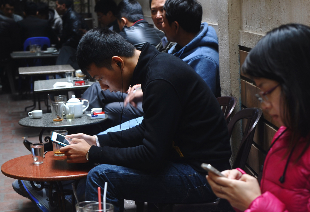 Customers use wireless devices at a coffee shop in downtown Hanoi on November 28, 2013.
