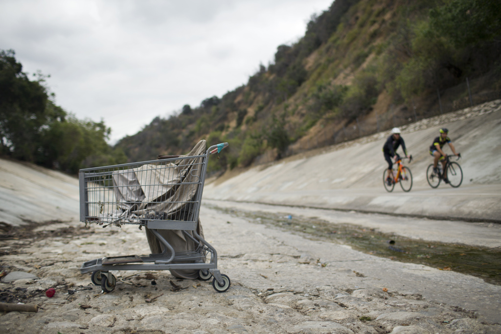 Bicyclists ride the Arroyo Seco trail on Tuesday morning, May 5, 2015 where several encampments line the riverbed.