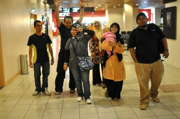A cheery group of travelers, the women in Muslim head scarves, or hijab, walks through an airport. April, 2009