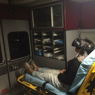 Fawn Quinn, one of the first people to experience Flatline, sits on a gurney in an ambulance while watching.