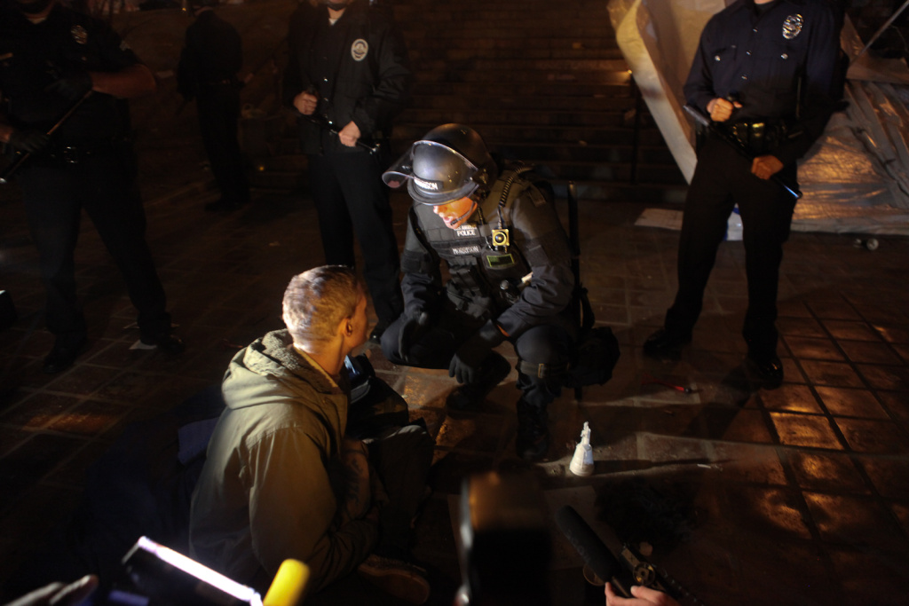 An LAPD officer warned a protester that he would be arrested if he didn't leave the police cordon in the center of the park.