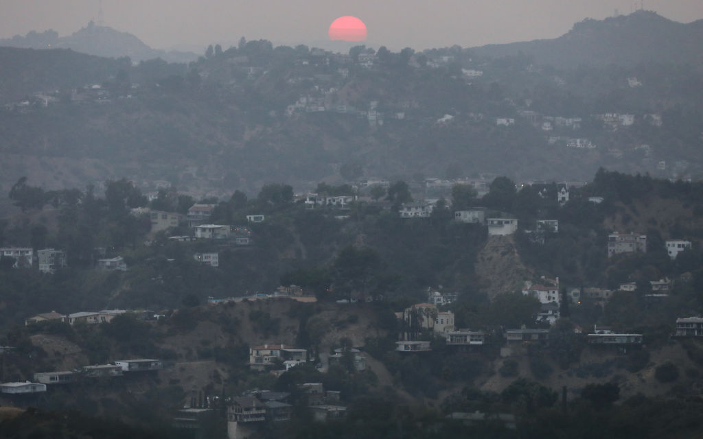 The sun sets amid smoke from wildfires on September 13, 2020 in Los Angeles, California.