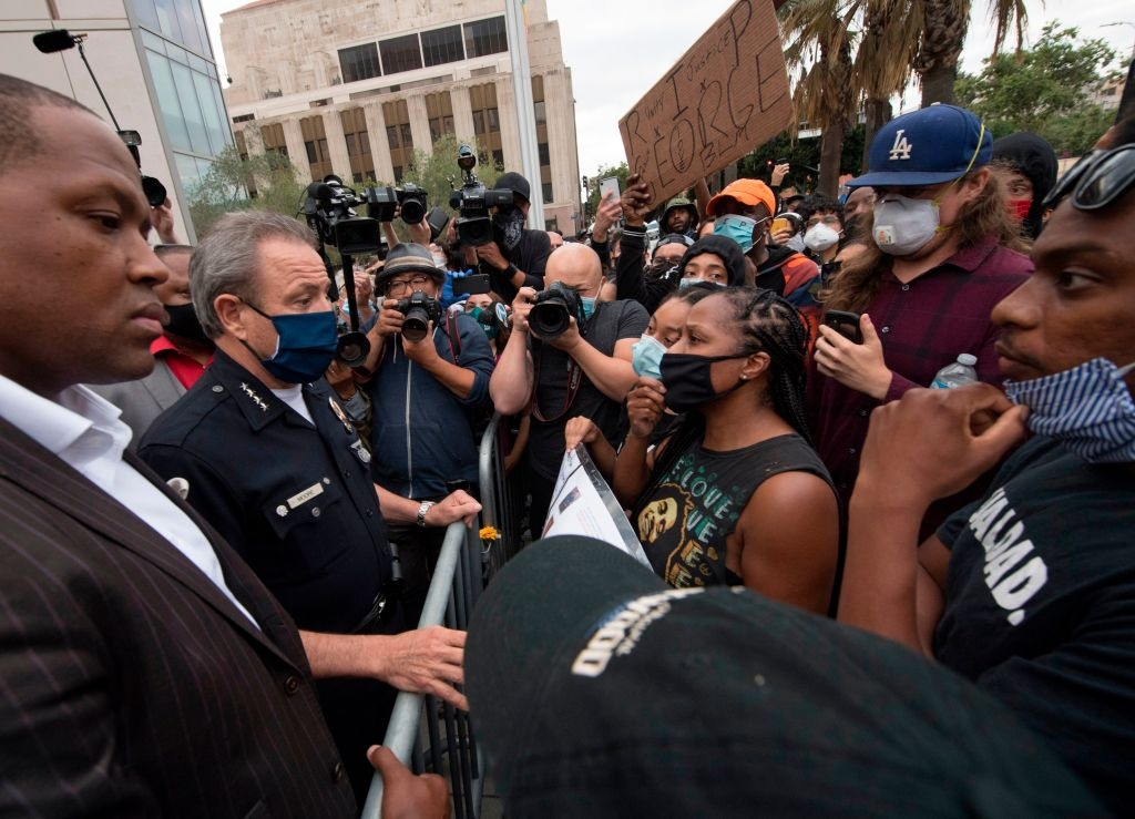 Los Angeles Police Chief Michel Moore (C) talks with Black Lives Matter members after a vigil for George Floyd at police headquarters in Los Angeles, California on June 5, 2020.