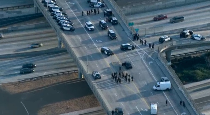 Police on an overpass over the 10 Freeway after anti-Trump protesters marched and blocked the freeway on Thursday, Nov. 10, 2016.
