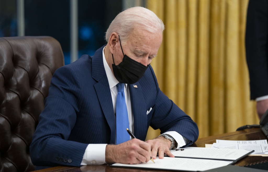President Biden signs an executive order on immigration in February in the Oval Office.