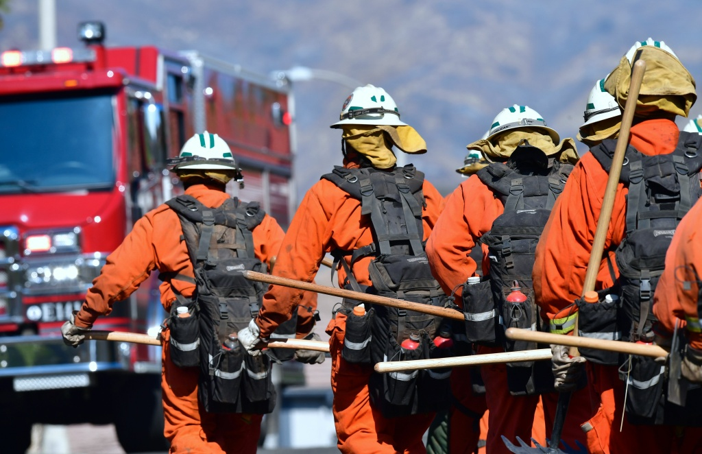 California's Volunteer Inmate Firefighters work as a group in West Hills, California on November 11, 2018, as they continue their battle to control the Woolsey Fire.