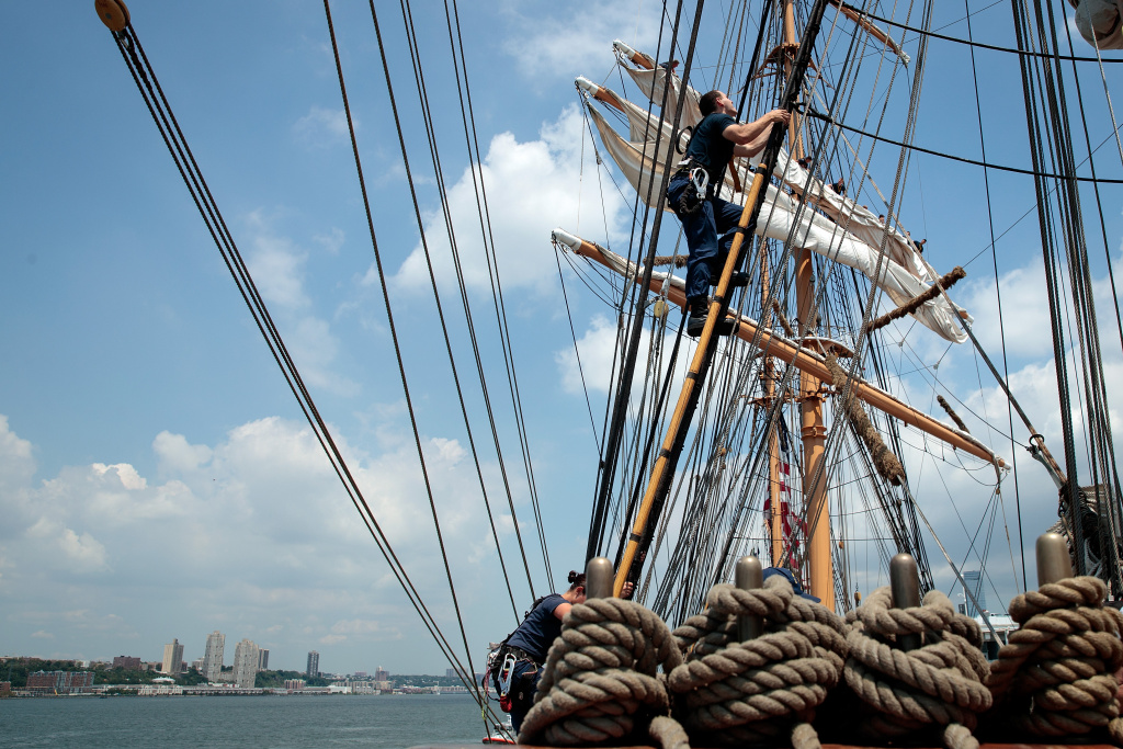 NEW YORK, NY - AUGUST 4: A member of the U.S. Coast Guard climbs up the ship to furl sail aboard the U.S. Coast Guard Cutter Eagle along the Hudson River next to the Intrepid Air and Space Museum, August 4, 2016 in New York City. Thursday is National U.S. Coast Guard Day in the United States. On this day 226 years ago, Alexander Hamilton requested Congress to create the U.S. Coast Guard. (Photo by Drew Angerer/Getty Images)
