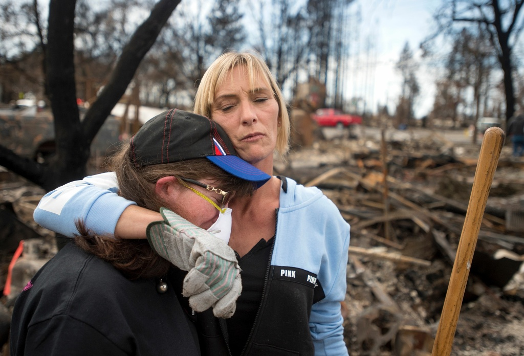 TOPSHOT - Tanya Williams (R) consoles her neighbour Dawn Lockhart (L) as they view their burned homes in the Coffey Park area of Santa Rosa, California, on October 20, 2017.   Residents are being allowed to return to their burned homes on October 20 to grieve and search through remains. Around 5,700 homes and businesses have been destroyed by the fires, the deadliest in California's history. / AFP PHOTO / JOSH EDELSON        (Photo credit should read JOSH EDELSON/AFP/Getty Images)