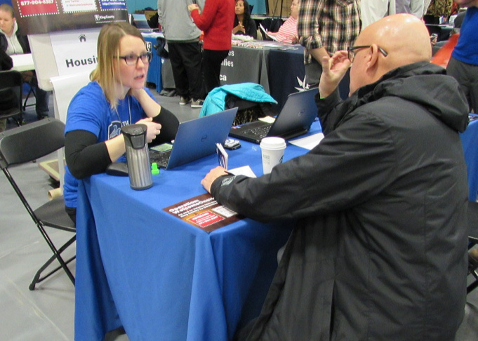 Dawn Barrett works with a veteran inquiring about housing at the Seattle Stand Down