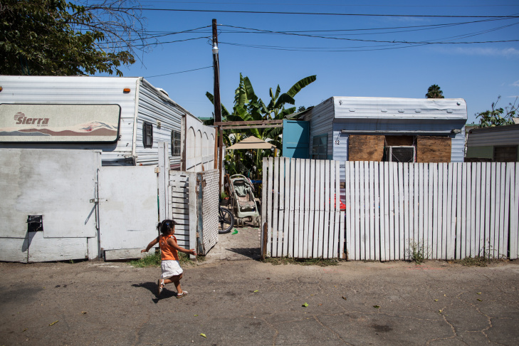 A toddler runs into the yard of her family's trailer home in Pomona. Many families in Pomona can't afford preschool – about 20 percent live in poverty.