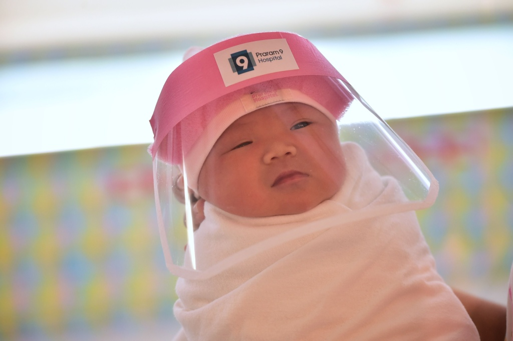 This photo taken through a glass window at a maternity ward shows a newborn baby wearing a face shield, in an effort to halt the spread of the COVID-19 coronavirus, at Praram 9 Hospital in Bangkok on April 9, 2020.