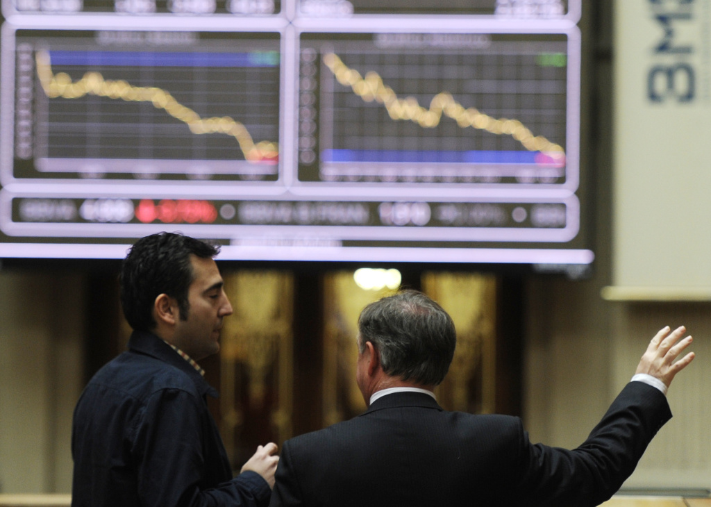 Men look at the IBEX-35 index curve on April 23, 2012 at Madrid's stock exchange. Top shares on the Madrid stock exchange slumped 3.24 percent in early trade, hammered by concerns over Spanish sovereign debt and the French presidential elections.