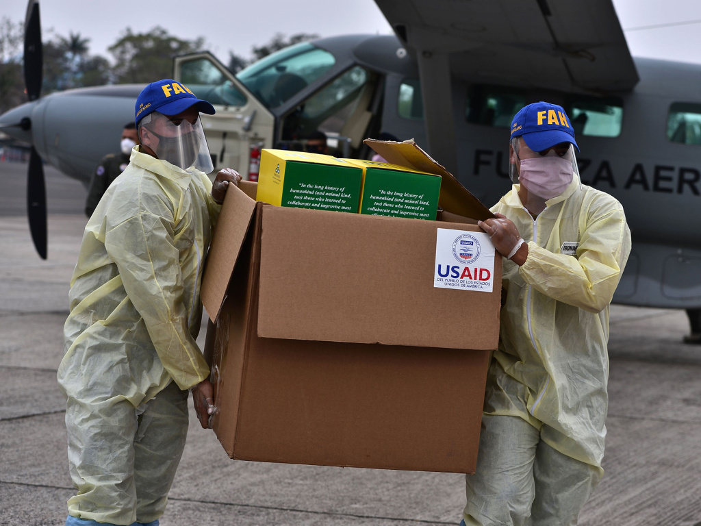 Foreign aid takes many forms — and Trump and Biden have differing perspectives. Above: Members of the Honduran Armed Forces carry a box of COVID-19 diagnostic testing kits donated by the United States Agency for International Development and the International Organization for Migration.