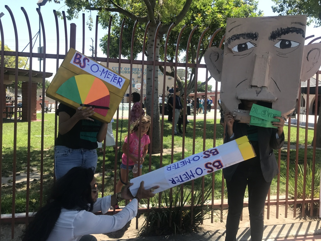 Environmental activists from the East Yards Communities for Environmental Justice pose with signs and protest materials depicting Governor Jerry Brown.