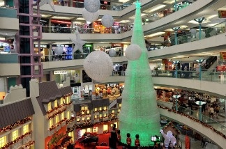 People shop in a shopping mall decorated with a giant Christmas tree made of 59,327 mineral water bottles.  Consumers spent and earned more in November, reflecting a rebound from the disruptions caused by Superstorm Sandy. The Commerce Department says consumer spending rose 0.4 percent compared with October. Personal income jumped 0.6 percent, the biggest gain in 11 months.