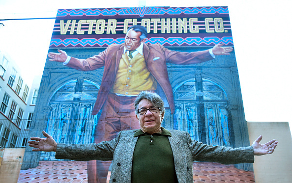 Muralist Eloy Torres mimicks the pose of Oscar-winning Actor Anthony Quinn on the 70-foot-tall