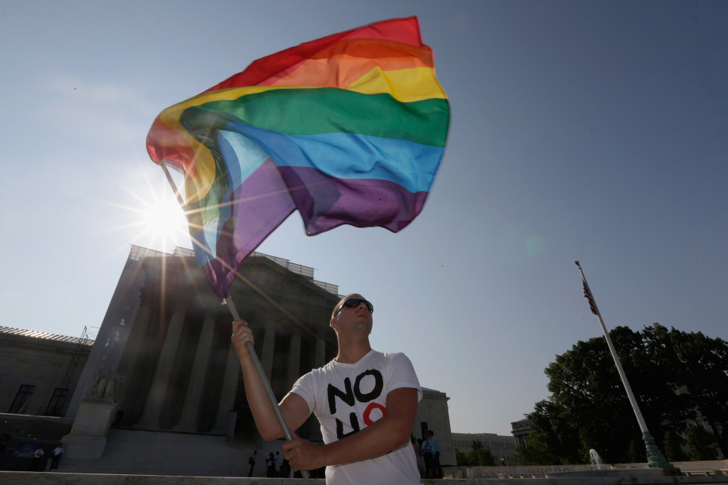 Gay rights activist Vin Testa of DC waves a flag outside the U.S. Supreme Court building in Washington, DC in January 2013.