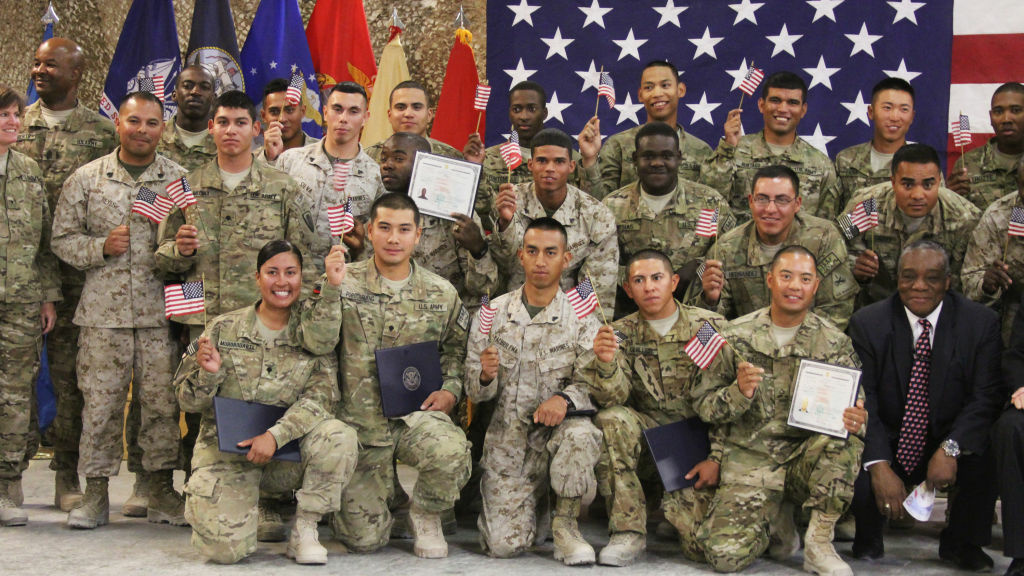 U.S. soldiers and Marines pose after being sworn in as U.S. citizens in a service in Afghanistan. A new Obama administration policy would spare some immigrant family members of U.S. military from deportation.
