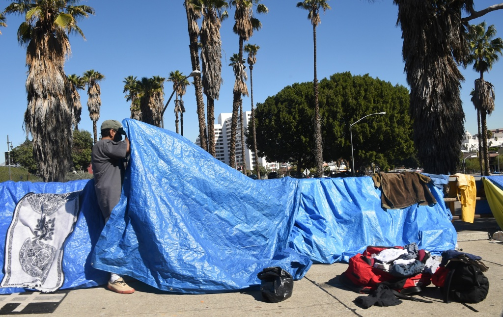 A homeless man fixes his tent along a street in Los Angeles.