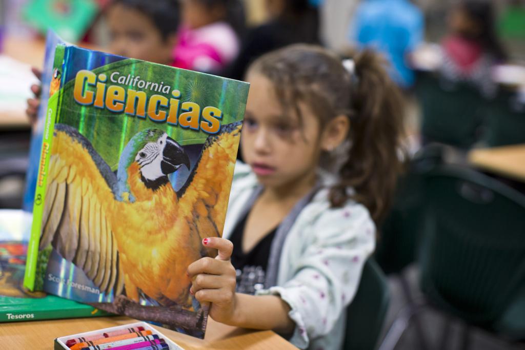 First grader Elizabeth Gatlardo reads a Spanish-language science textbook at George Brown Elementary, a dual-language school in San Bernardino, on Monday morning, May 4, 2015.