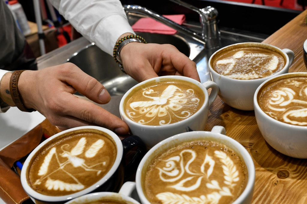 A barista shows off their latte art skills on a cappuccino during a trade show in Rimini, Italy on January 21, 2018.