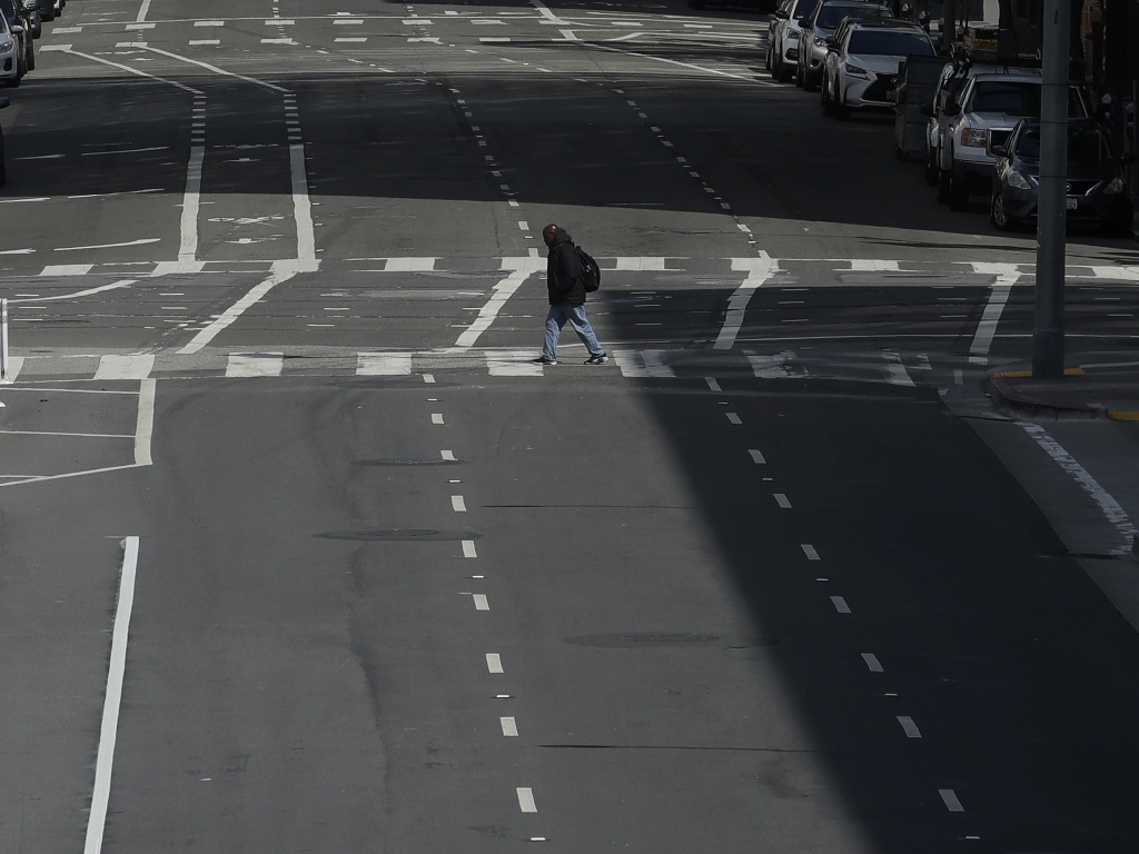 A man crosses a nearly empty street in San Francisco, on March 17, 2020. Despite a reduction in driving last year, road fatalities increased, according to the National Safety Council.