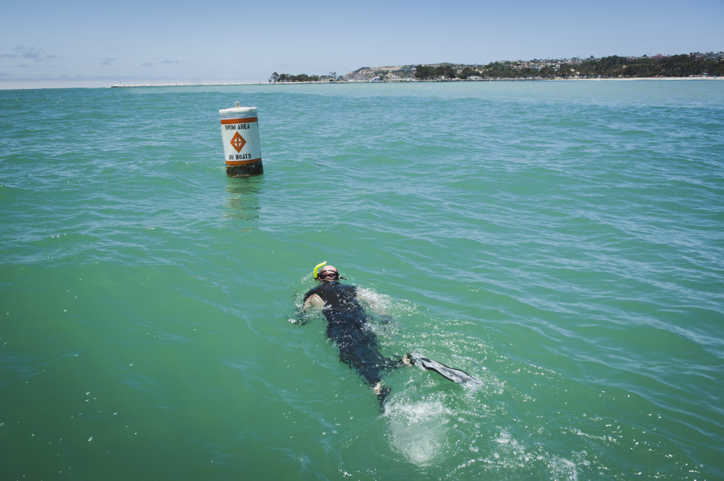 Shark researcher Chris Lowe of California State University, Long Beach swims to a buoy to attach a device that collects information from sharks that the team has tagged for a research project on shark behavior near Dana Point, June 28, 2017.