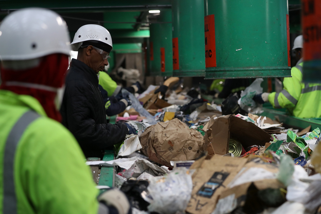 Workers sort through cardboard and mixed paper at Recology's Recylce Central on January 4, 2018 in San Francisco, California.