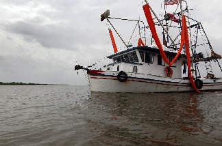 An oil skimming boat returns to port after inclement weather forced them to abandoned the effort to clean up oil from the Deepwater Horizon oil spill in the Gulf of Mexico on July 2, 2010 in Terrebonne Bay, Louisiana.
