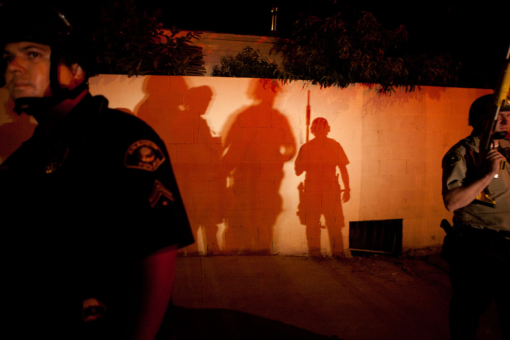 Police officers stand guard after protesters set fire to a near by trash bin during a demonstration to show outrage for the fatal shooting of Manuel Angel Diaz, 25, at Anaheim City Hall on July 24, 2012 in Anaheim, California. Diaz was fatally shot on July 21 by an Anaheim police officer and has sparked days of protests by the angered community.