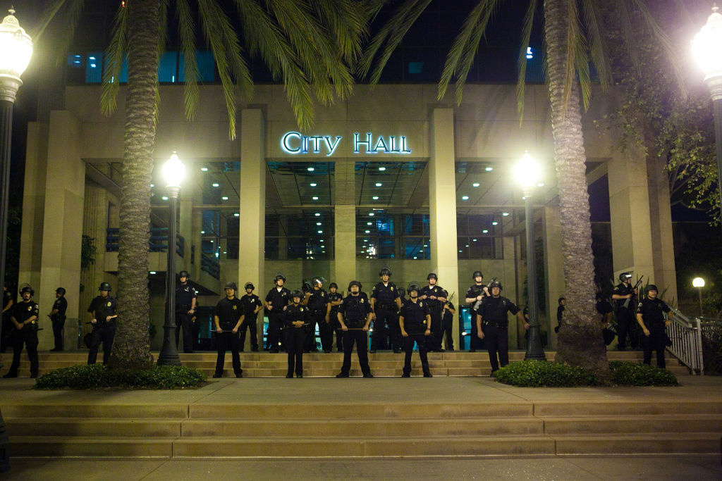A line of police officers protect Anaheim City Hall during demonstrations to show outrage for the fatal shooting of Manuel Angel Diaz, 25, at Anaheim City Hall on July 24, 2012 in Anaheim, California. Diaz was fatally shot on July 21 by an Anaheim police officer and has sparked days of protests by the angered community.