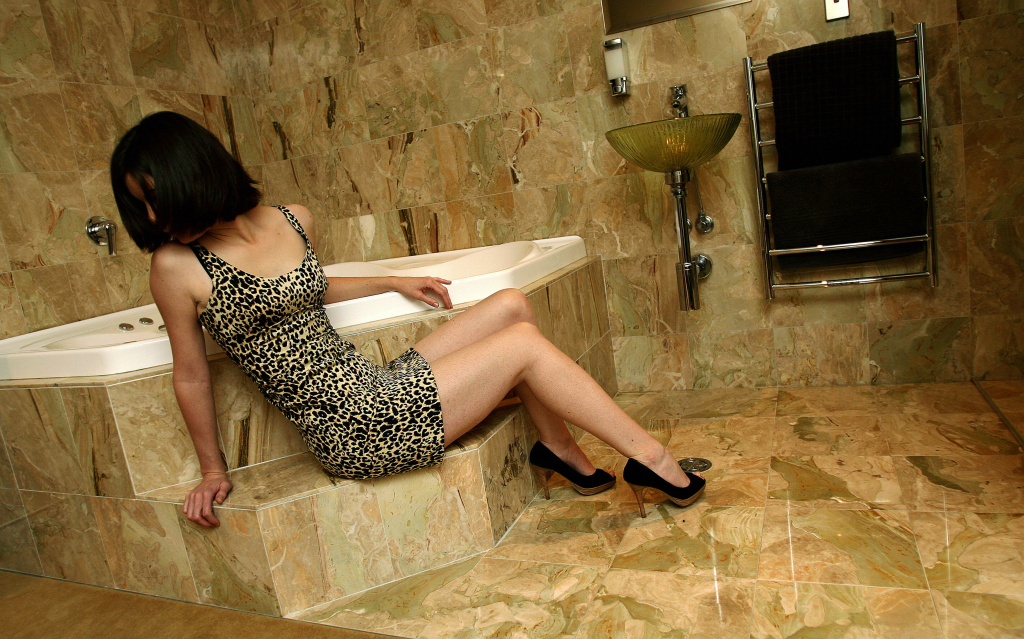A sex worker poses on marble tiling, the same as that used in the Trump Tower in New York, in a room at the upmarket Xclusive brothel in Sydney's Bondi Junction on July 1, 2008.