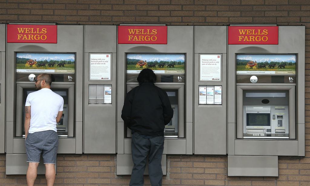 Customers use ATMs at a Wells Fargo Bank branch office on July 12, 2012 in Daly City, California.
