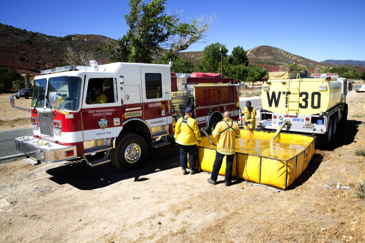 Nicole White is a forest technician with the San Bernardino National Forest working on the Pilot Fire behind Ryan Nuckols' home in Hesperia California on Aug. 9, 2016.