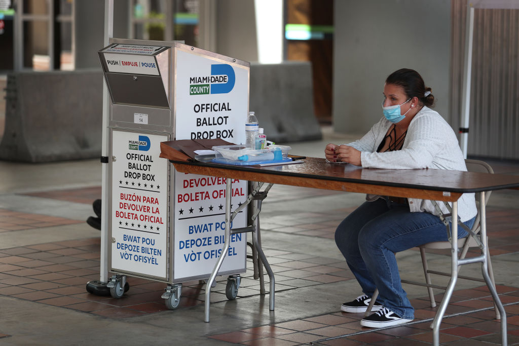 A poll worker waits for voters to help them put their mail-in ballot in an official Miami-Dade County ballot drop box on August 11, 2020 in Miami, Florida.